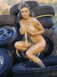 Carmen Electra posing on tires