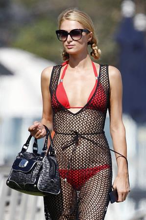 Paris Hilton at the beach in a skimpy red bikini and fishnet kaftan in Malibu.July 12, 2013