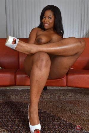 Monique Symone spreads her legs on a couch