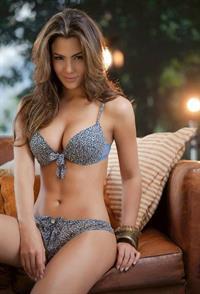 Natalia Vélez sitting outside in a bikini